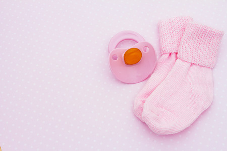 Pink Baby Background, Pink baby socks with soother on pink and white polka dot background with copy-space for your message