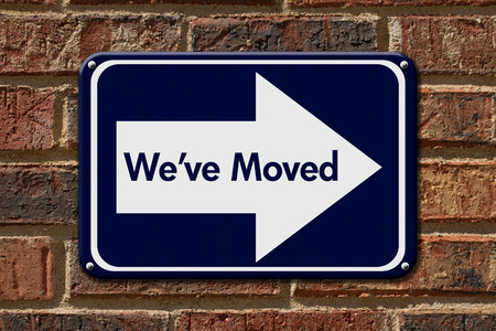 moved: We have Moved Sign,  A blue sign with the word Weve Moved with an arrow on a brick wall