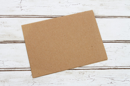 brown: Blank Card for your message, A brown card that is blank over a distressed wood background Stock Photo