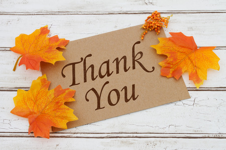 you: Thank You Card, A brown card with words Thank You over a distressed wood background with Autumn Leaves