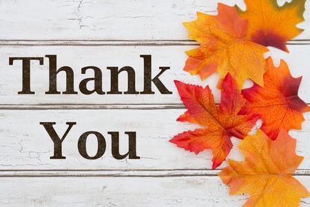 agradecimiento: Gracias escrito en el fondo de madera del grunge con las hojas de otoño