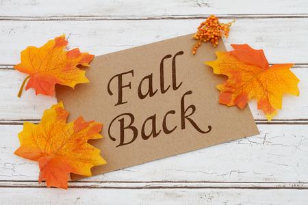 back: Cae detr�s Card, una tarjeta de color marr�n con palabras Fall Volver sobre un fondo de madera apenado con las hojas de oto�o