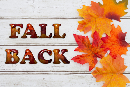 fall time: Fall Back written on grunge wood background with Autumn Leaves Stock Photo