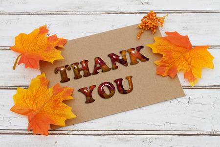 caes: Gracias tarjeta, una tarjeta de color marrón con las palabras gracias sobre un fondo de madera apenado con las hojas de otoño Foto de archivo