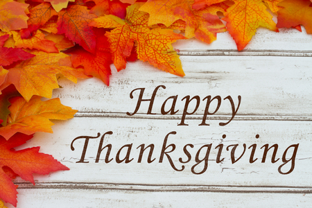 Happy Thanksgiving written on grunge wood background with Autumn Leaves