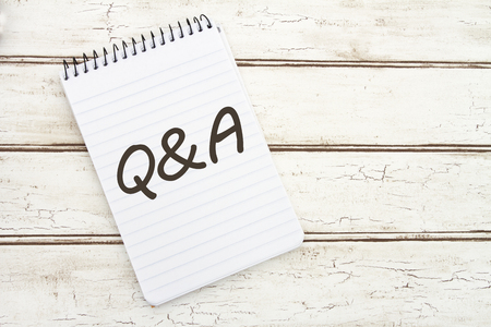 qa: Questions and Answers, A spiral Notepad that has the words Q&A over a distressed wood background