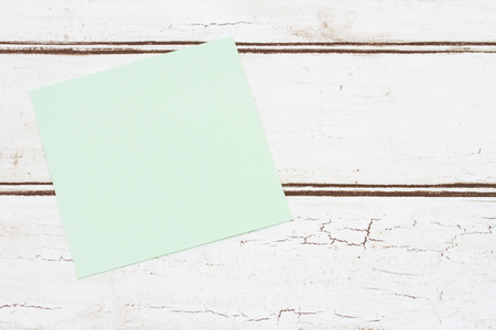 note board: Blank Sticky Note for your message, A Green Sticky Note that is blank over a distressed wood background Stock Photo