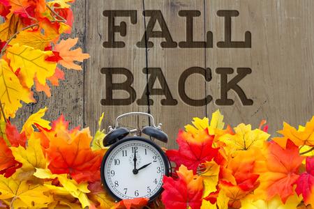Descenso del tiempo de cambio, las hojas de otoño y despertador con madera del grunge y las palabras Fall Volver
