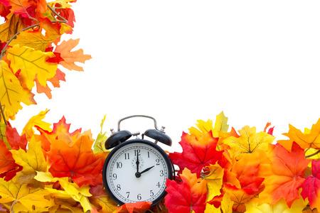 Tiempo: Hojas de otoño de fondo, las hojas de otoño y reloj de alarma aislado en blanco con espacio para su mensaje