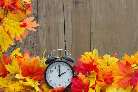 reloj: Hojas de oto�o de fondo, las hojas de oto�o y reloj de alarma con la madera del grunge con espacio para su mensaje