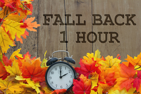 in the back: Fall Time Change, Autumn Leaves and Alarm Clock with grunge wood with text Fall Back 1 Hour Stock Photo