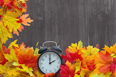 change of seasons: Autumn Leaves Background, Autumn Leaves and Alarm Clock with grunge wood with space for your message
