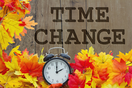 Fall Time Change, Autumn Leaves and Alarm Clock with grunge wood with text Time Change