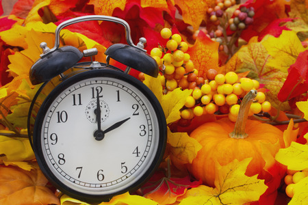 clock: Autumn Time Change, Autumn Leaves and Alarm Clock with a pumpkin Stock Photo