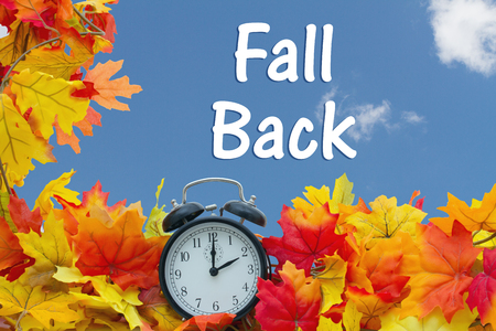 Fall Time Change, Autumn Leaves and Alarm Clock with sky background with text Fall Back