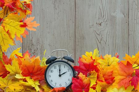 orologi antichi: Autumn Leaves e sveglia con legno del grunge con spazio per il messaggio Archivio Fotografico