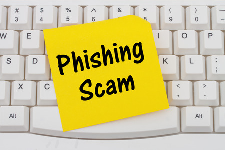 web scam: Computer Keyboard with a yellow blank sticky note with text Phishing Scam