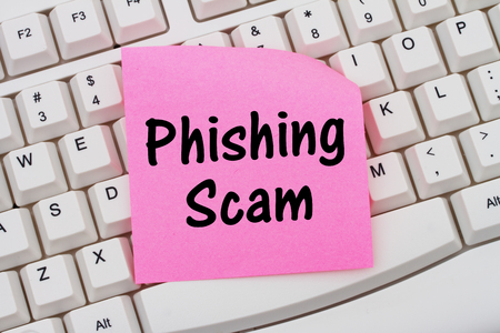 web scam: Phishing Scam, Computer Keyboard with a pink blank sticky note with text Phishing Scam Stock Photo