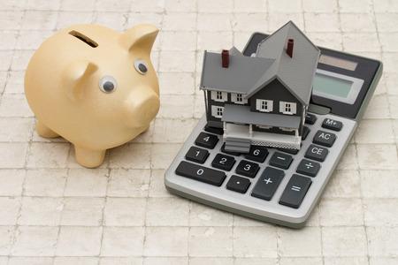 住宅のコスト、灰色の家、貯金箱、石の背景上の電卓