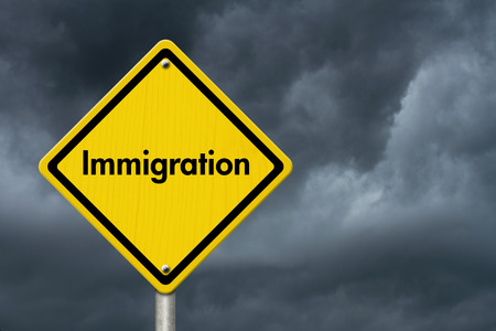 illegal immigrant: Immigration Road Sign, Yellow Caution sign with word Immigration with stormy sky background