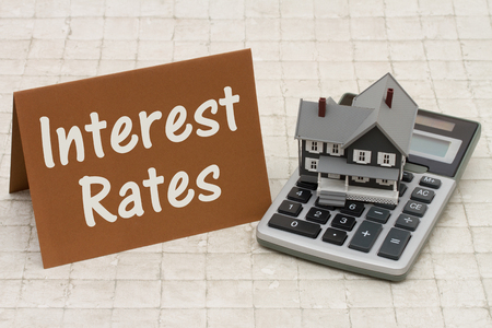 mortgage rates: Mortgage Interest Rates, A gray house, brown card and calculator on stone background with text Interest Rates