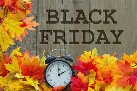 Time for Black Friday Shopping, Autumn Leaves and Alarm Clock with grunge wood with text Black Friday