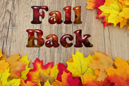 fall time: Fall Back, Fall Leaves over a distressed wood background with text Fall Back