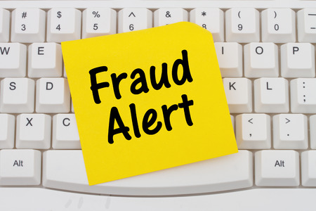 alert: Fraud Alert, Computer Keyboard with a yellow blank sticky note with text Fraud Alert