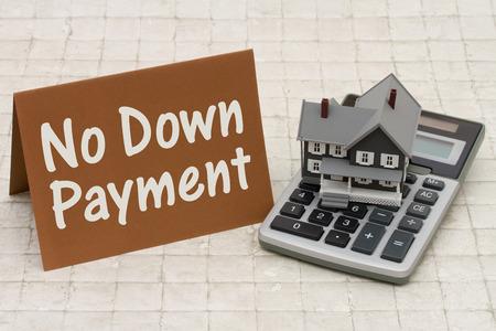 calculadora: Inicio Hipoteca Sin Pago Inicial, Una casa gris, marr�n y tarjeta de la calculadora en el fondo de piedra con el texto sin pago Foto de archivo