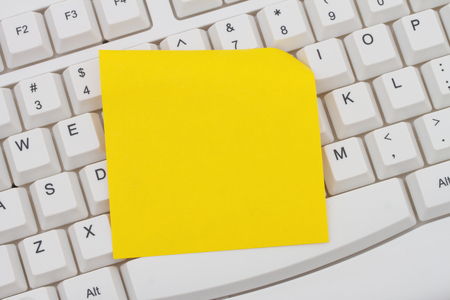 computers online: Computer Keyboard with a yellow blank sticky note for your personalized message