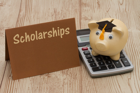 Getting a scholarship, A golden with grad cap piggy bank, card and calculator on a wood background with text Scholarships Stock Photo