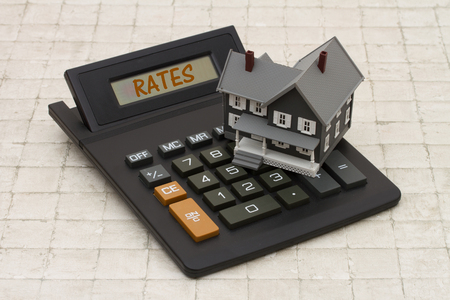 mortgage rates: Home Mortgage Interest Rates, A gray house and calculator on stone background with text Rates