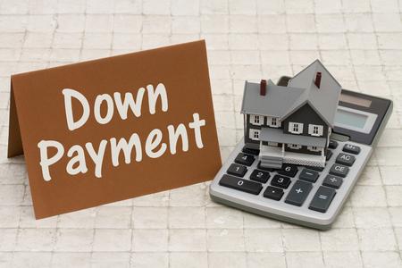 Home Mortgage aanbetaling, Een grijze huis, bruine kaart en rekenmachine op steen achtergrond met tekst Vooruitbetaling