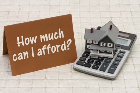 afford: Home Mortgage Affordability, A gray house, brown card and calculator on stone background with text   How much can I afford