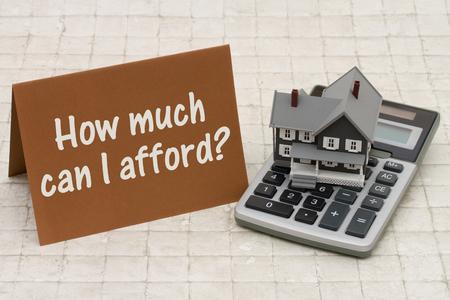 Home Mortgage Betaalbaarheid, Een grijze huis, bruine kaart en rekenmachine op steen achtergrond met tekst Hoeveel kan ik veroorloven