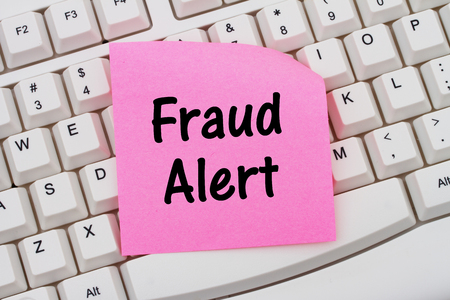 web scam: Fraud Alert, Computer Keyboard with a pink blank sticky note with text Fraud Alert Stock Photo