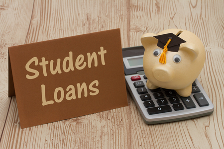 grad: Getting Student Loans, A golden with grad cap piggy bank, card and calculator on a wood background with text Student Loans