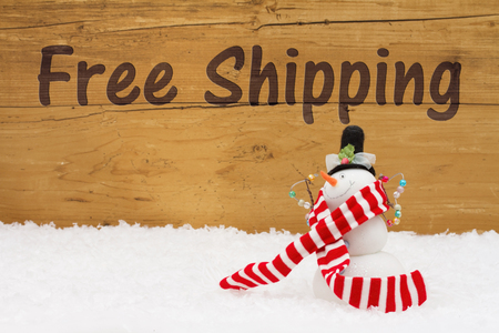 snowman wood: Free Shipping, A Snowman on snow with a weathered wood background and text Free Shipping Stock Photo