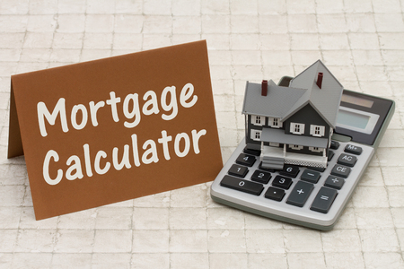 Home Mortgage Calculator, A gray house, brown card and calculator on stone background with text  Mortgage Calculator Imagens
