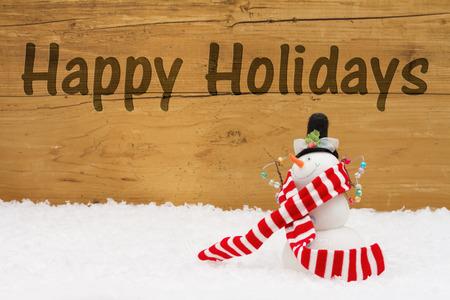 Happy Holidays Message, een sneeuwpop op sneeuw met een verweerde houten achtergrond en de tekst Happy Holidays