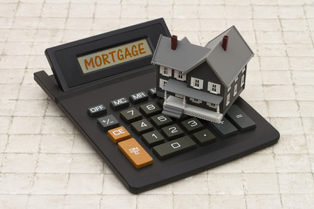Home Mortgage, szary dom i kalkulator na tle kamienia hipoteką tekstu