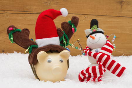 snowman wood: Christmas Savings, Piggy Bank and Snowman with scarf on snow with a weathered wood background