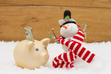snowman wood: Christmas Savings, Piggy Bank and Snowman with scarf on snow with a weathered wood background and copy-space for your message
