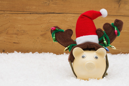 christmas savings: Christmas Savings, Piggy Bank with reindeer antlers on snow with a weathered wood background and copy-space for your message