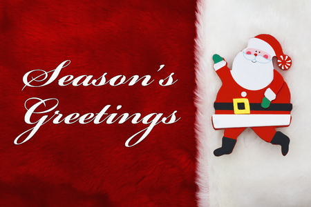 st nick: Seasons Greetings, A plush red stocking a Santa Claus and words Seasons Greetings Stock Photo