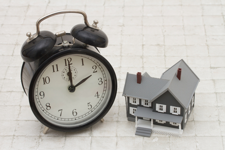 Time to buy a house, A gray house and black alarm clock on stone background 스톡 콘텐츠