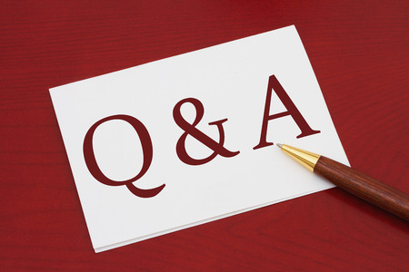 Where to get Q & A , White Greeting card with text Q & A on a red wood background