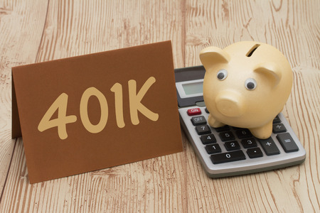 Having a 401k plan, A golden piggy bank, card and calculator on wood background with text  401k Standard-Bild
