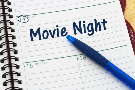 a day planner with blue pen with text Movie Night Stock Photo