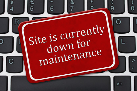 computer net: A red and white sign with the words Site is currently down for maintenance on a keyboard